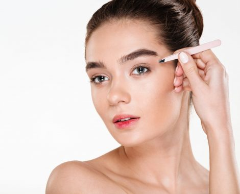 Close up studio portrait of young brunette woman with soft skin plucking eyebrows with tweezers, isolated over white background